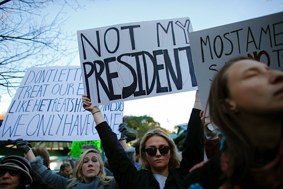 A woman holds a poster during a rally against US President-elect Donald Trump in Union Square, New York, 12 November