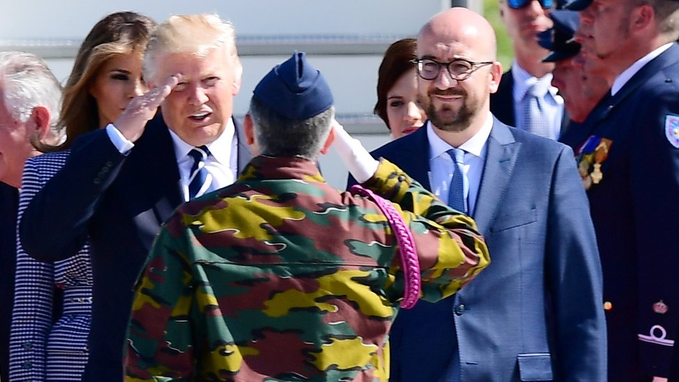 US President Donald Trump (L) and Belgian Prime Minister Charles Michel (R) stand in front of a military serviceman upon arrival at the Melsbroek military airport in Steenokkerzeel on May 24, 2017