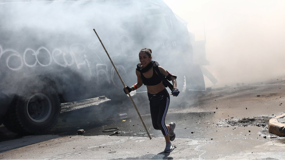 A demonstrator runs from tear gas during a protest against Chile's state economic model in Santiago October 20, 2019
