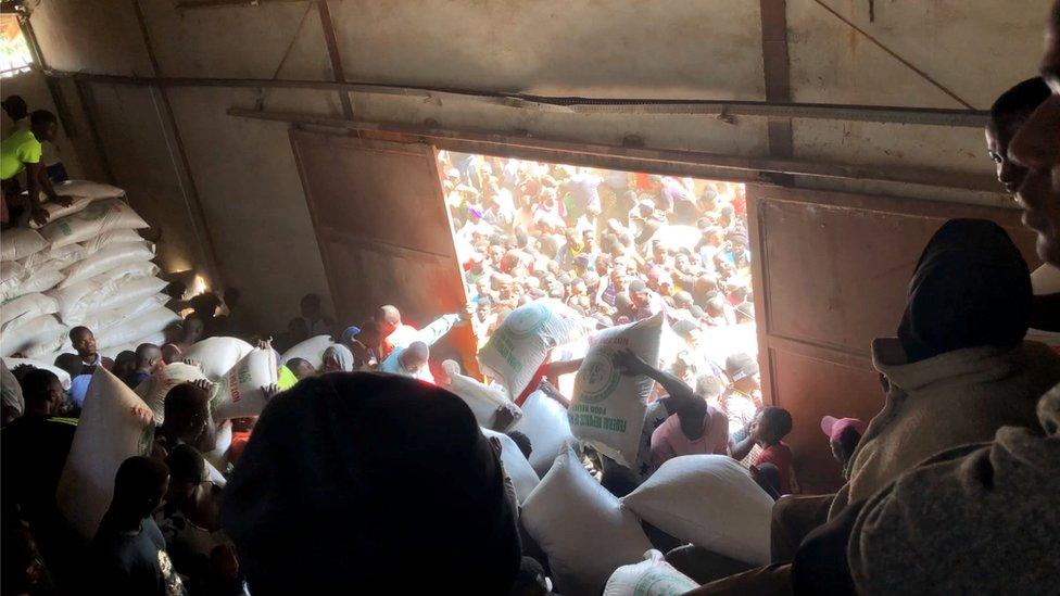 People carry sacks of supplies at a warehouse in Bukuru, Nigeria, 24 October 2020