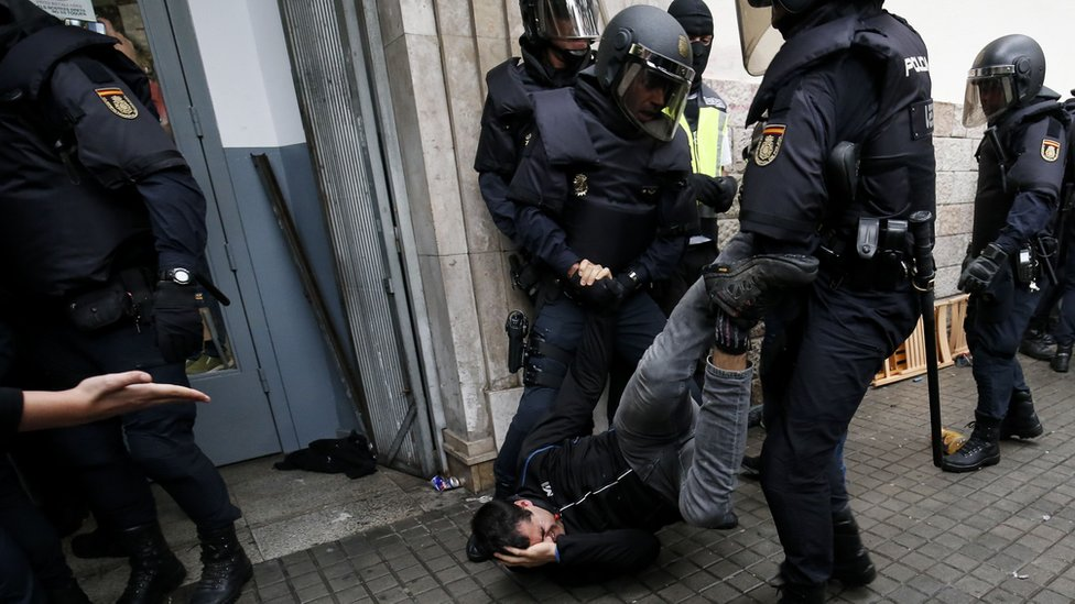A man, lying on the ground, clutches his head in pain as he is dragged through the street by his legs by two police officers in full riot gear
