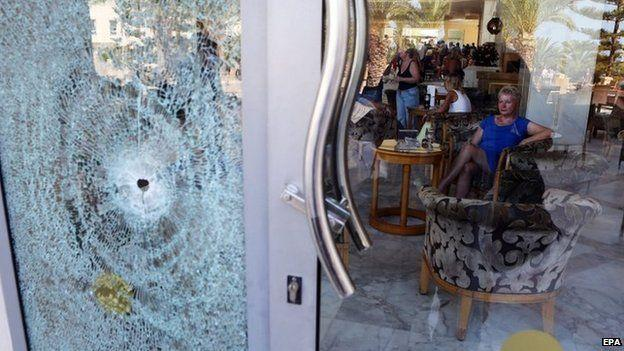 A tourist at the Imperial Marhaba Hotel sits near a door shattered by a bullet