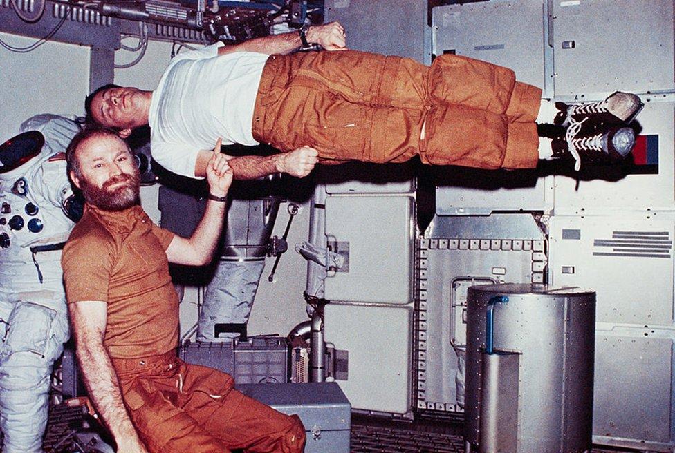 Jerry Carr finge sostener con un dedo a un Ed Gibson que flota sin gravedad