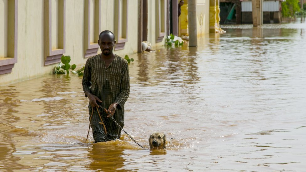 A Sudanese man wades through the floodwaters with his dog at Umm Dawm district in Khartoum, Sudan on September 8, 2020.