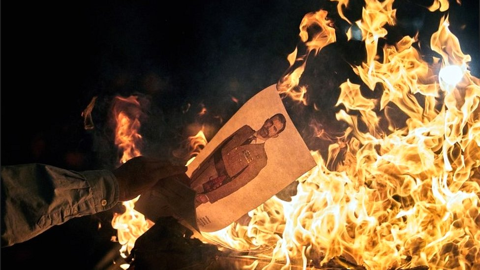 Catalan pro-independence protesters burn a picture of Spain's King Felipe VI in Catalonia on 4 November 2019