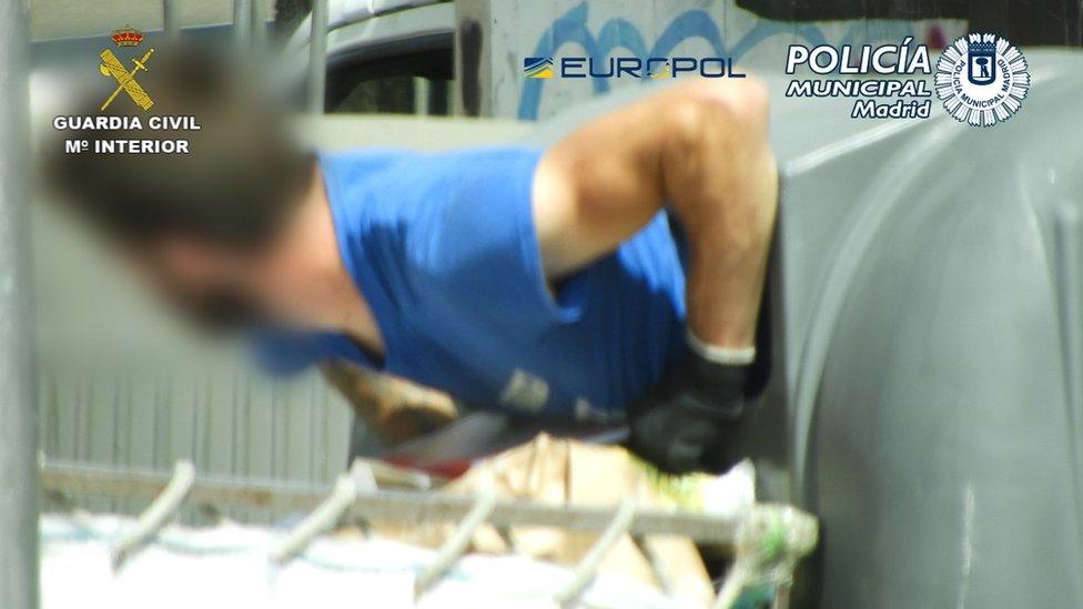 Seorang pria keluar dari tempat sampah di Madrid.