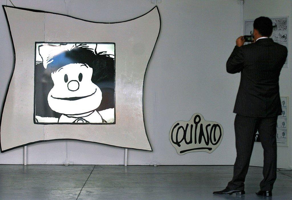 Un hombre fotografía una caricatura de Mafalda.