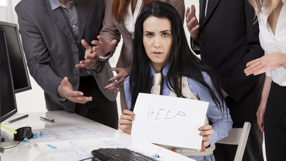 Woman sitting among business colleagues holding up paper with word 'help' written on it