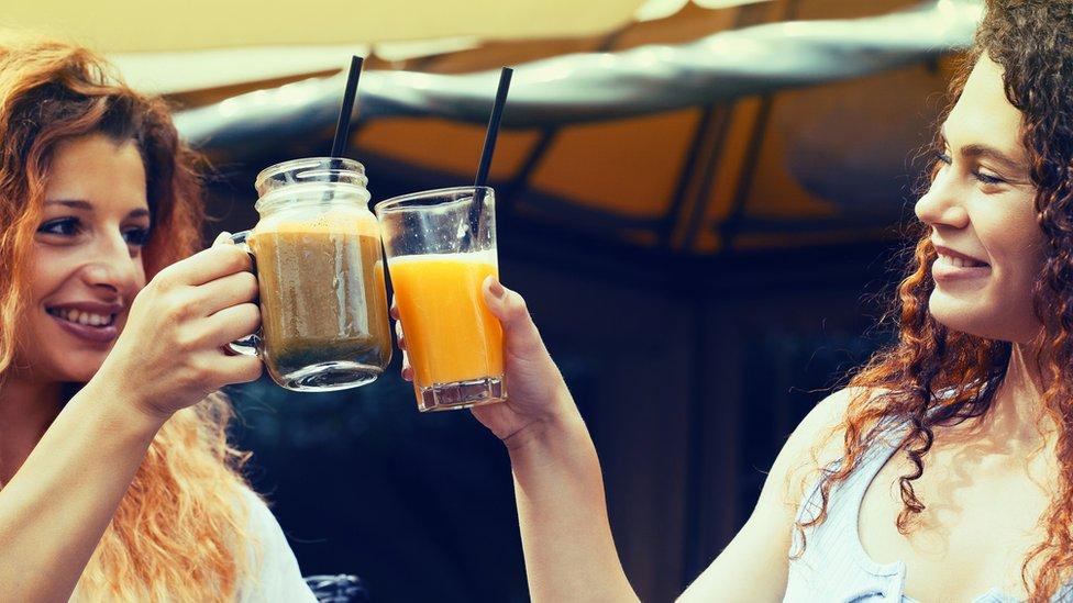 Dos mujeres brindan con jugos.