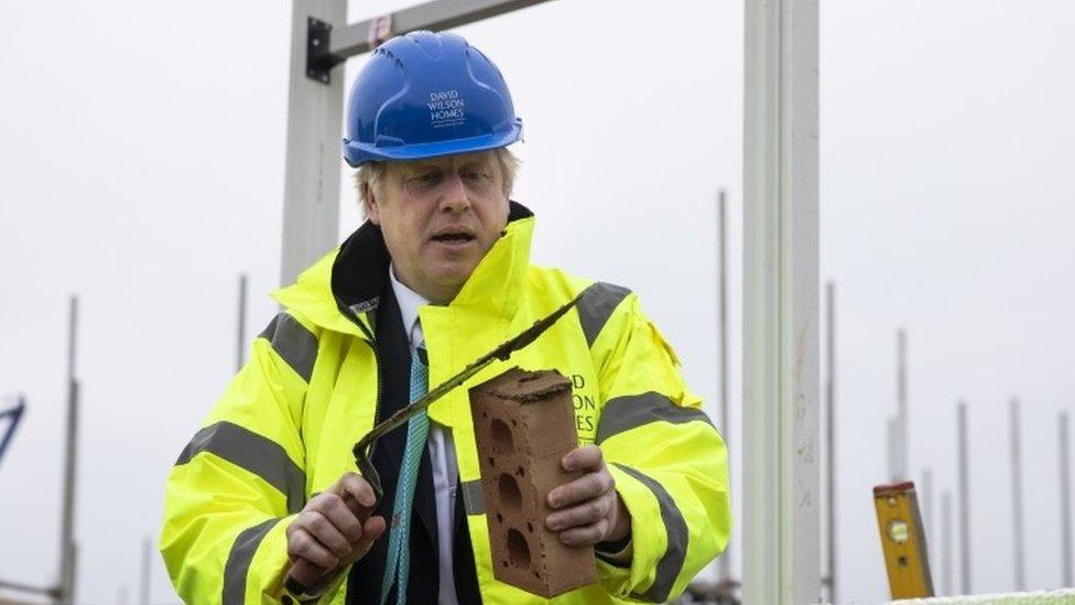 Boris Johnson prepares to lay a brick