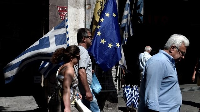 People walk past Greek and WU flags in Athens
