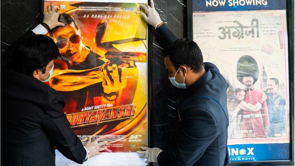 Pekerja memasang poster film di teater sebelum jadwal pembukaan kembali bioskop pada 15 Oktober