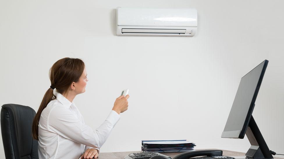 Mujer en una oficina ajustando el equipo de aire acondicionado con un control remoto