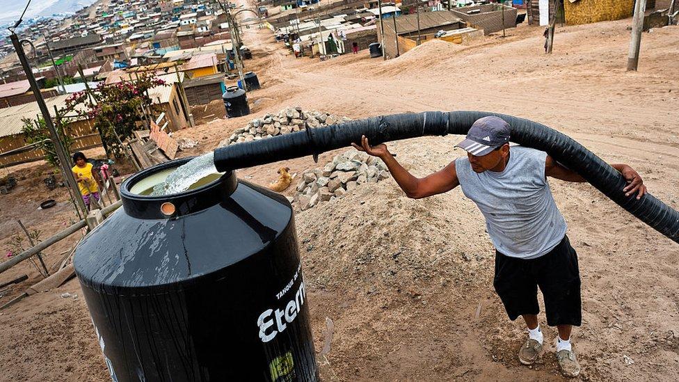 Hombre llenando un tanque con agua.