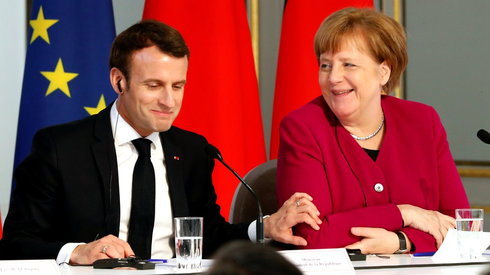 Mr Macron, smiling to himself, places a hand on Mrs Merkel's arm while she laughs at something as the pair sit at a table during a joint news conference