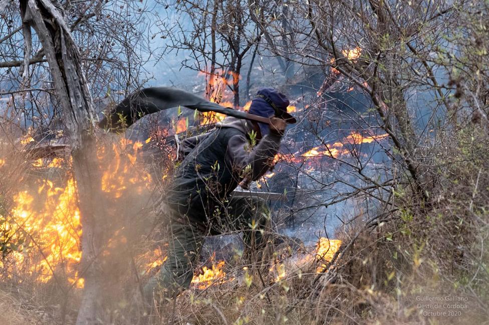 Un hombre apagando fuegos con un chicote
