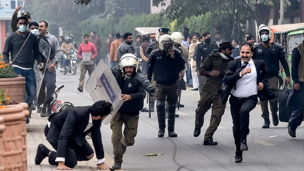 Police chase lawyers following a clash between lawyers and doctors in Lahore on December 11, 2019
