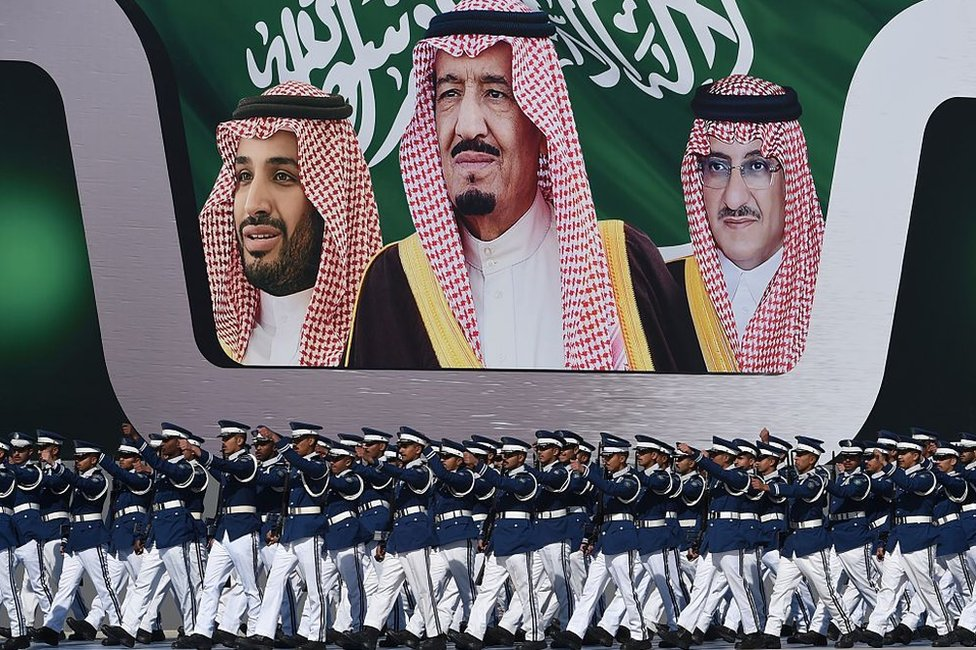 Newly graduated Saudi air force officers march in front of a banner bearing portraits of King Salman (C), then Crown Prince Mohammed bin Nayef (R), and then deputy Crown Prince Mohammed bin Salman at King Salman airbase in Riyadh on 25 January 2017