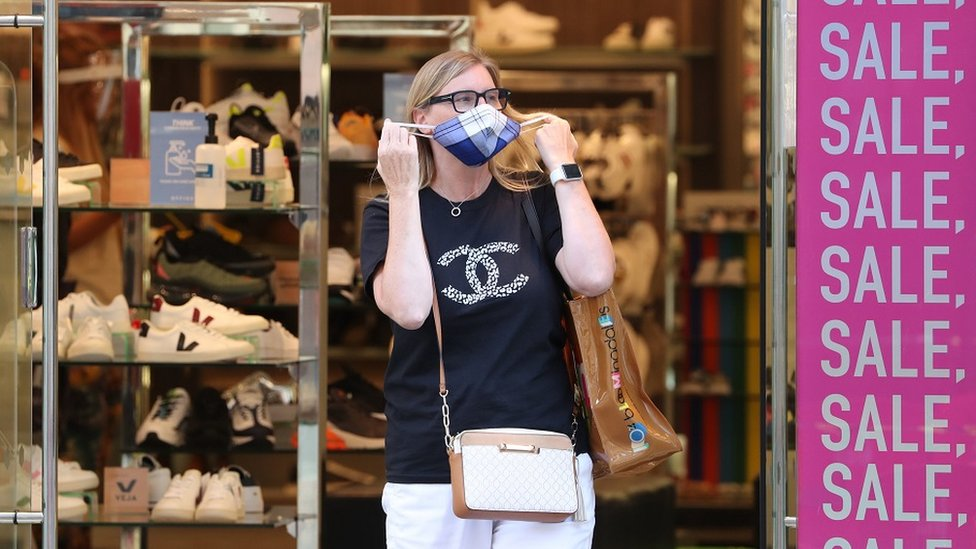 A woman leaving a shop with a mask on