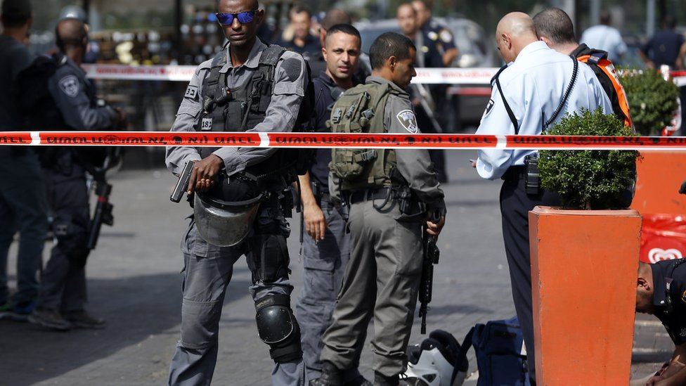 Israeli security forces near the body of a Palestinian shot after police said he stabbed two people in Jerusalem, 10 October 2015