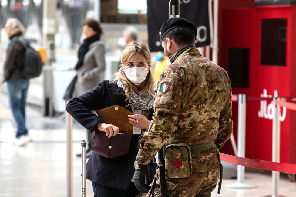 A woman wearing a face mask speaks to a soldier