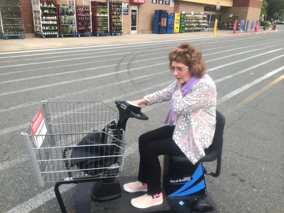 Kathleen riding a motorised shopping cart at US store Walmart