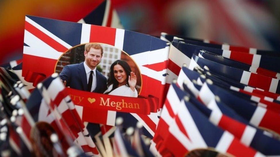 Banderas con la imagend e Meghan Markle y el príncipe Harry.