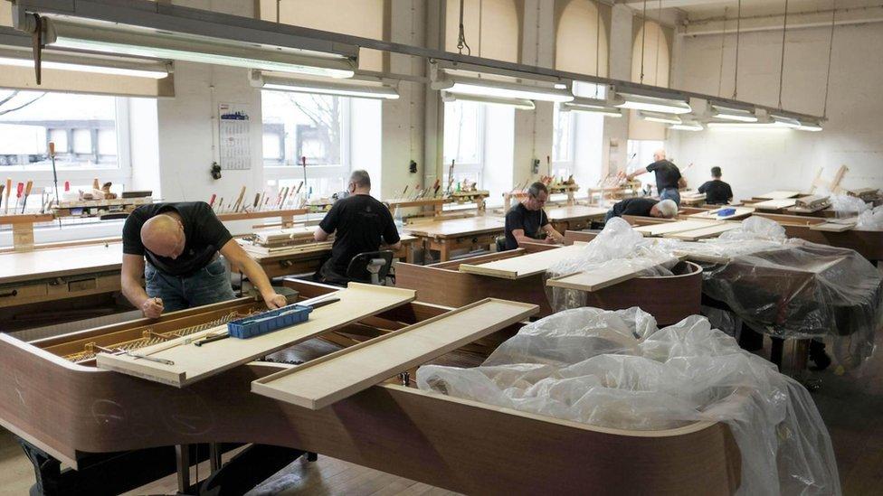 Trabajadores en una fábrica de pianos.