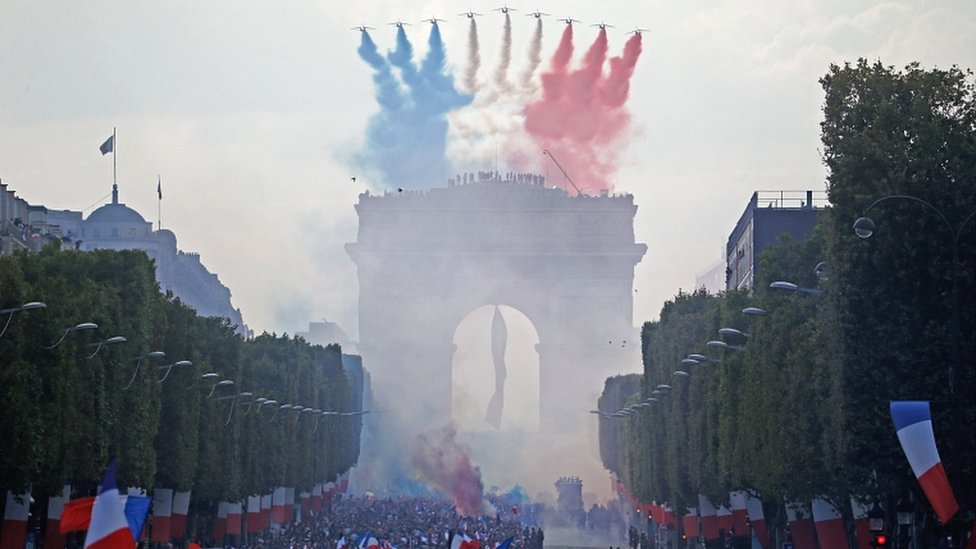 The Patrouille de France jets, trailing smoke in the colours of the national flag, fly over the Champs-Elysées on 16 July 2018 in Paris