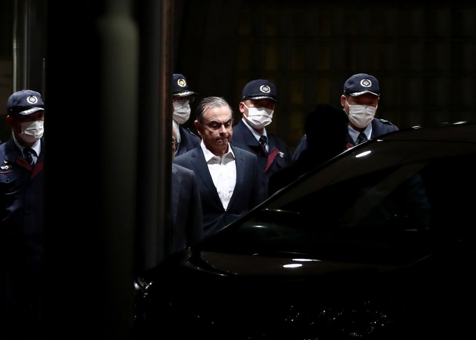 Former Nissan chairman Carlos Ghosn is escorted out of the Tokyo Detention House in April following his release on bail for multiple charges of financial misconduct.
