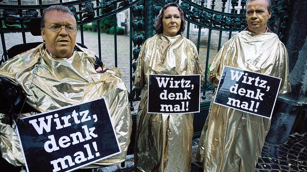 Personas protestan cubiertos por bolsas doradas