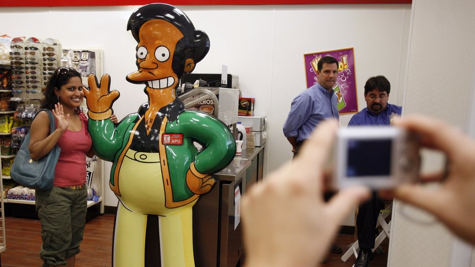 A woman poses for a photograph alongside a cartoon statue of the character Apu