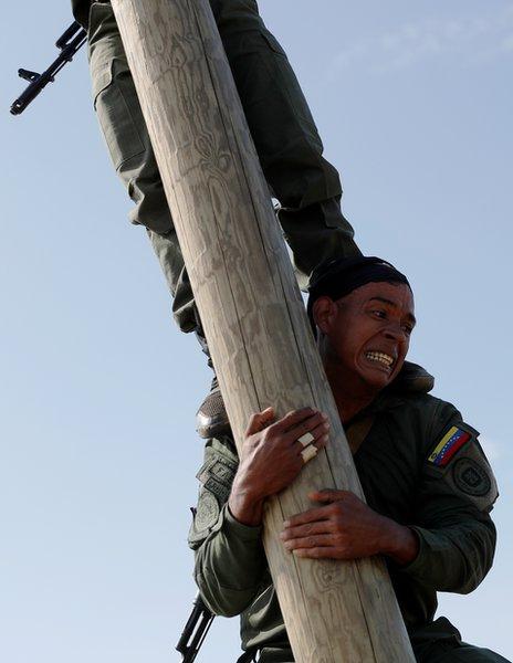 委內瑞拉陸戰隊員組成人梯,攀登電線桿。