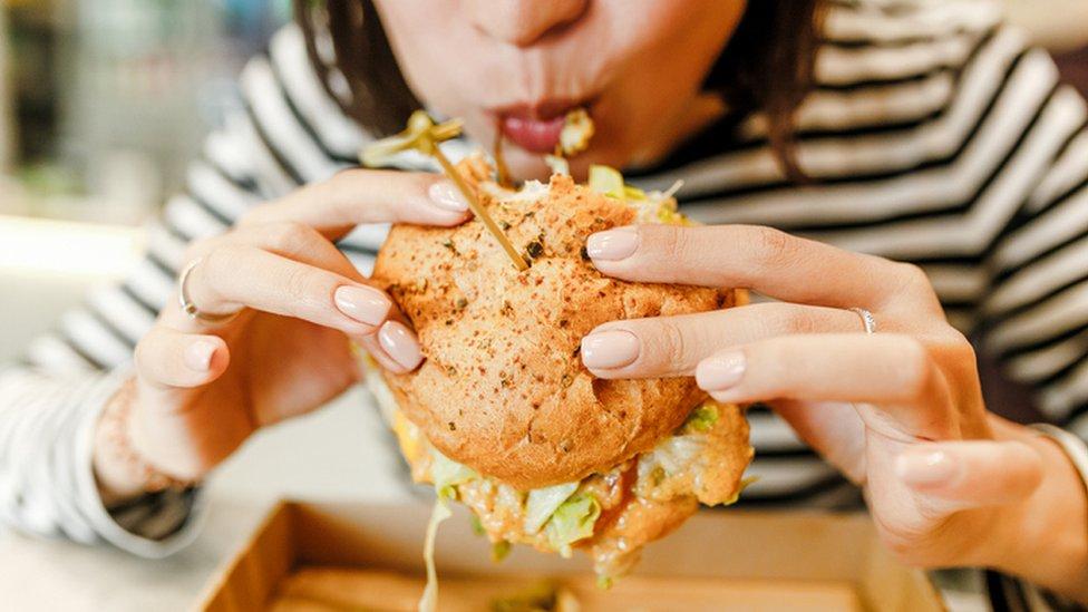 Una mujer come una hamburguesa.,