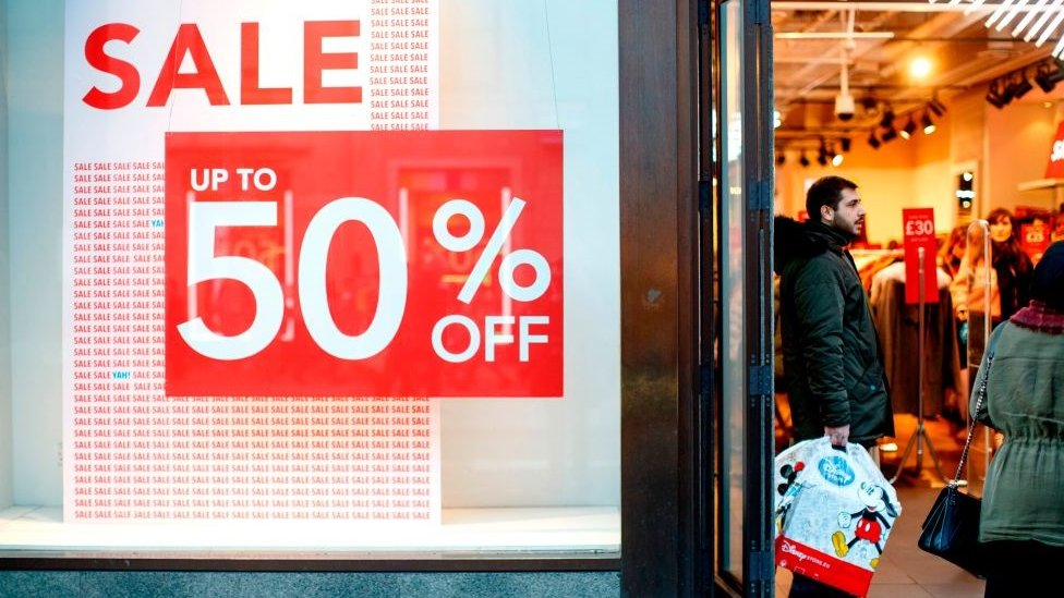 A shopper stands in the door of a shop advertising sale discounts on Oxford Street in London on December 13, 2018 less than two weeks before Christmas.