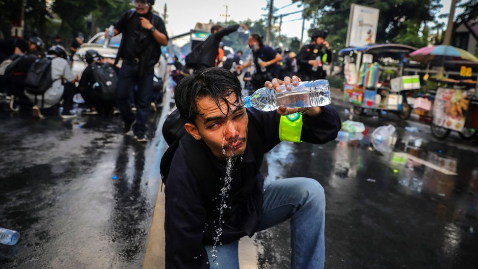 A protester who was exposed to tear gas washes his face outside parliament on 17 November 2020 in Bangkok