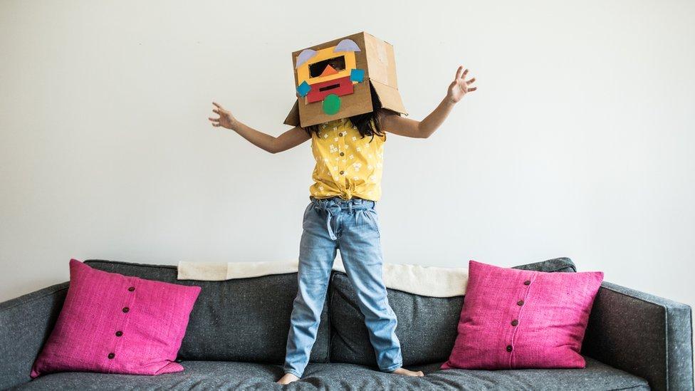 Niña con una caja de cartón decorada en la cabeza.