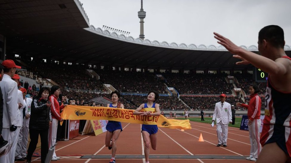 Kim Hye Gyong, right, narrowly beats her twin Kim Hye Song in the women's professional marathon