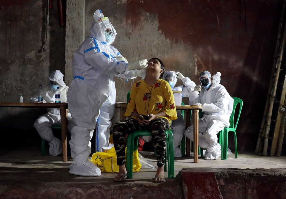 A healthcare worker wearing personal protective equipment takes swab from a woman