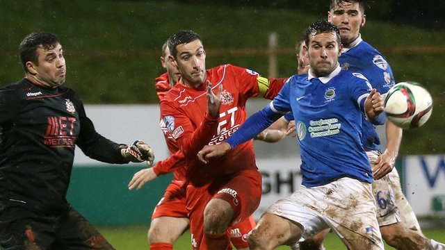 Portadown keeper David Miskelly challenges Linfield striker Andrew Waterworth for the ball