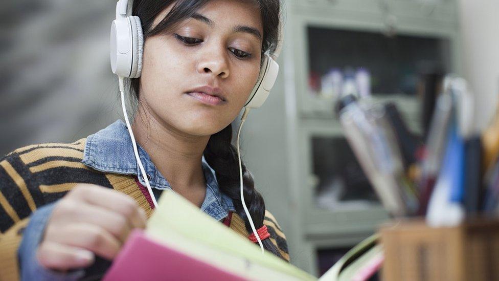 Una mujer estudia con auriculares.