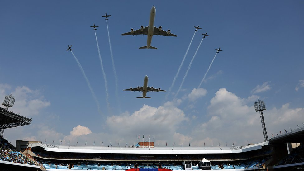 Two large planes and a fleet of small ones flying over the stadium
