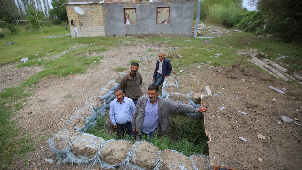 Local residents gather outside a dugout in readiness to take shelter during the fighting over the breakaway region of Nagorno-Karabakh, 30 September 2020