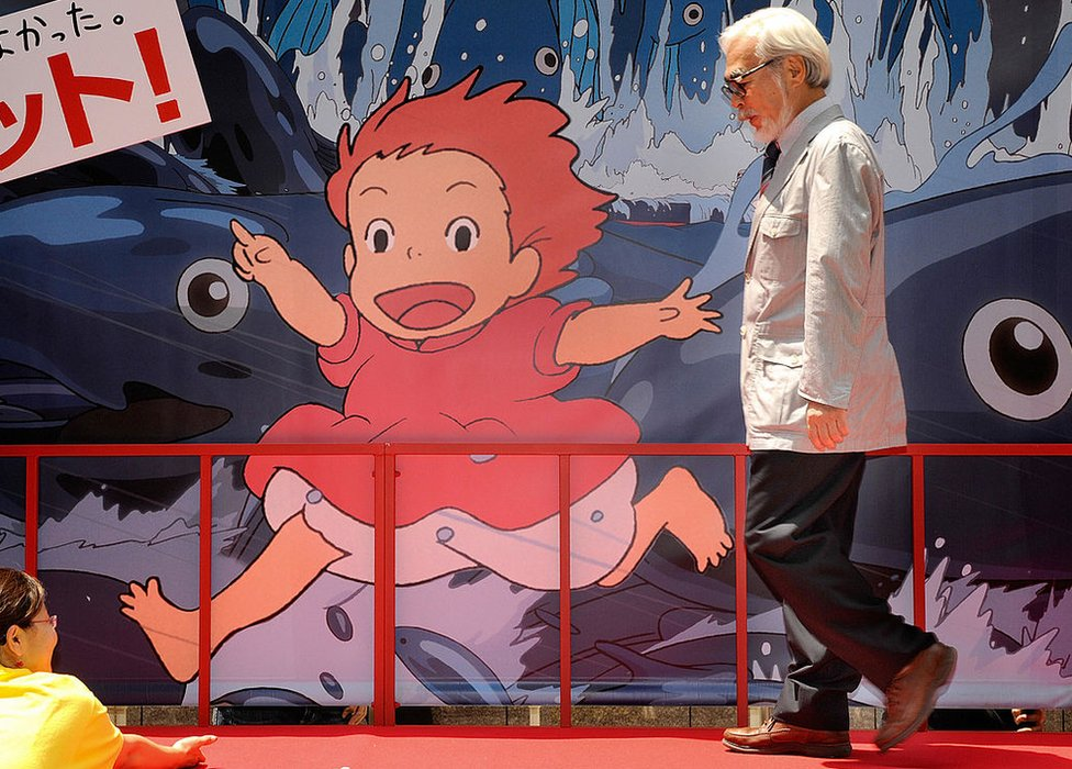 Oscar-winning Japanese animator and film director Hayao Miyazaki walks past a advertising board for a photo session following the release of his new animated movie 'Ponyo on the Cliff by the Sea' at a theater in Tokyo on 19 July 2008.