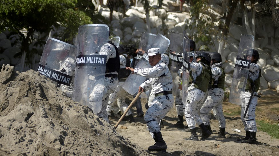 Members of Mexico's National Guard hold their shields to block migrants