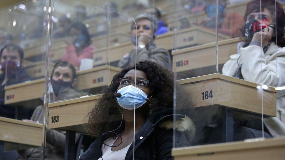 مضاربون في مزاد للزهور بـ جوهانسبرغ في جنوب أفريقيا في الثامن من مايو/أيار. المضاربون تفصل بينهم حواجز بلاستيكية في محاولة للوقاية من فيروس كورونا المستجد