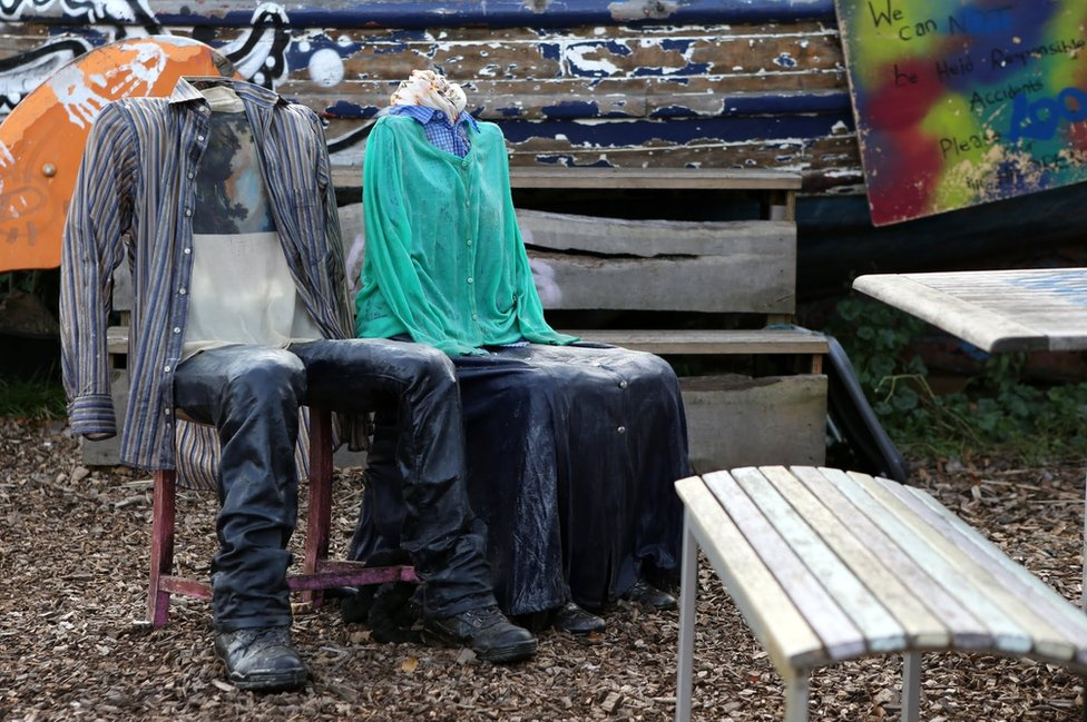 Two chairs are dressed in clothing, one in shirt and trousers and the other in a skirt and a cardigan