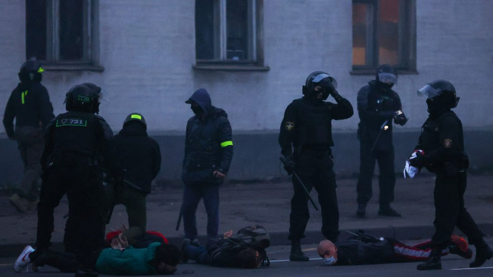 Police hold demonstrators face-down on the floor on 25 October