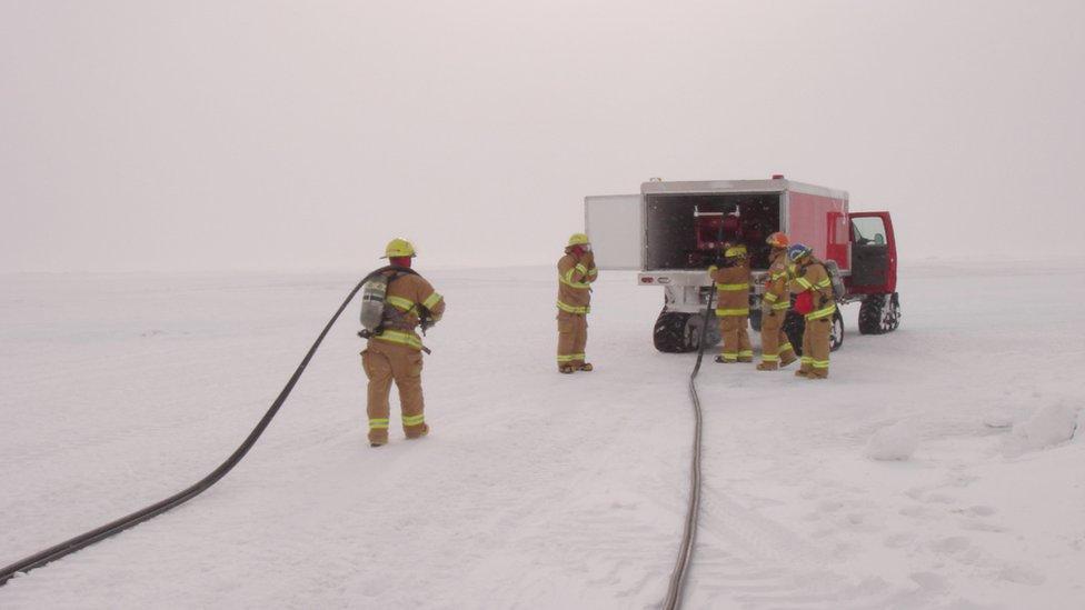 Cinco bomberos cargando mangueras cerca de un vehículo estacionado en el hielo.