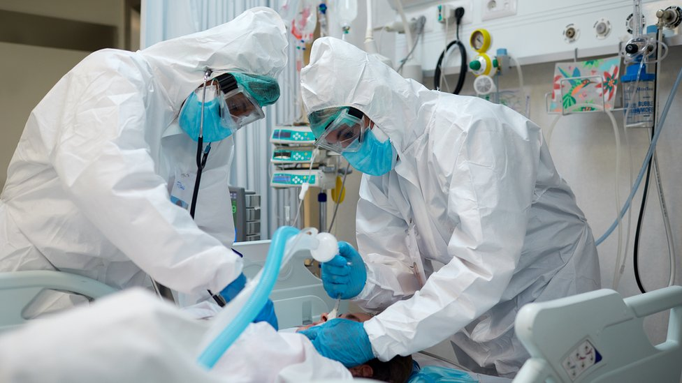 doctors in hazmat suits and masks treat patient